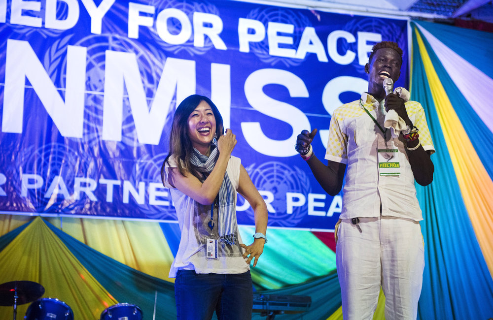 "Comedian, Feel Free, invites UNMISS peacekeeper, Catherine Shin, to the stage during the ""Comedy for Peace"" event, supported by the United Nations Mission in South Sudan (UNMISS), at the Nyakuron Cultural Centre on Sunday, 23 April in Juba."