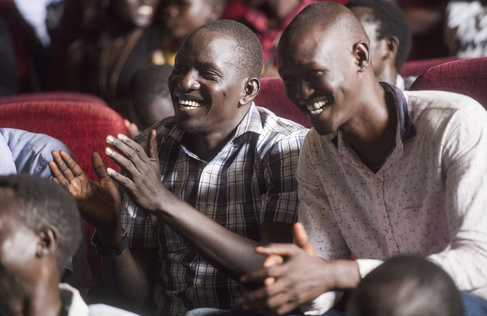 "Audience members laugh while attending ""Comedy for Peace,"" an event supported by the United Nations Mission in South Sudan (UNMISS), held at the Nyakuron Cultural Centre on Sunday, 23 April in Juba."