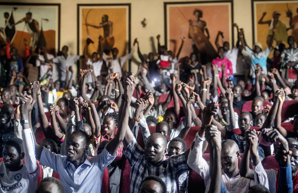 "Audience members join hands while attending ""Comedy for Peace,"" an event supported by the United Nations Mission in South Sudan (UNMISS), held at the Nyakuron Cultural Centre on Sunday, 23 April in Juba."