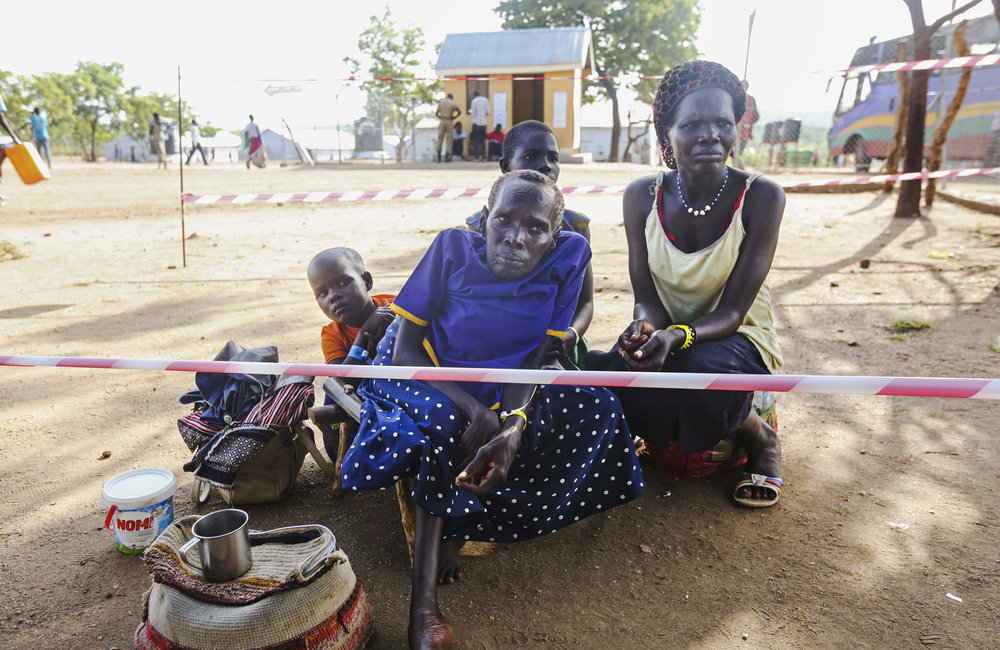 Newly arrived South Sudanese refugees wait for a wheelchair at the reception center at the Imvepi Refugee camp on Friday, 23 June, 2017 in Northern Uganda.