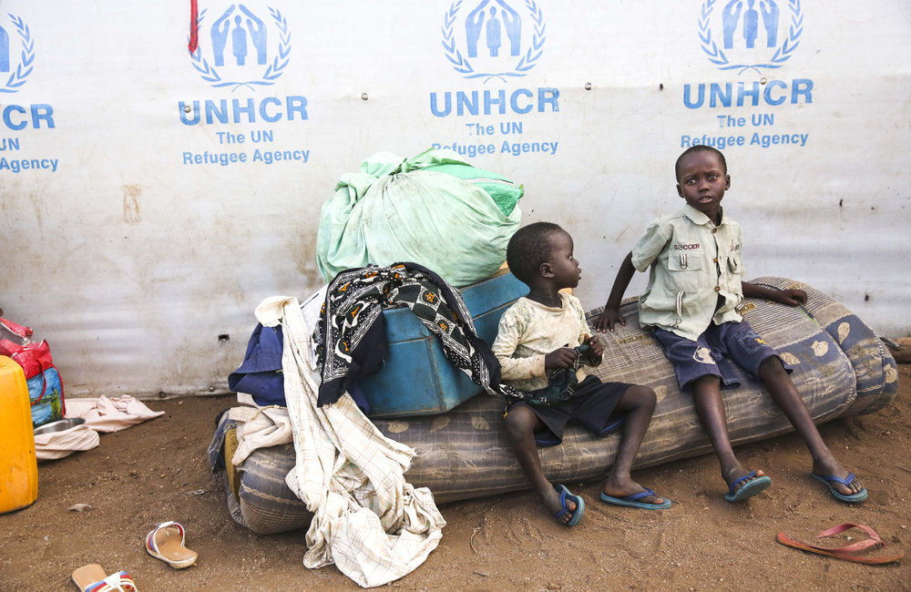 Young boys watch over their families belongings near the reception center at the Imvepi Refugee camp on Friday, 23 June, 2017 in Northern Uganda.  Recent arrivals to the camp are given temporary accommodations outside the center before receiving a designated plot of land.
