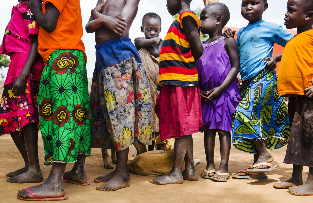 Young children wait to be processed at the Busia collection point near the Uganda/South Sudan border before their final destination of the Impvepi Refugee Camp on Friday, 23 June, 2017 in Busia, Uganda.  UNHCR reports 59 % of those arriving in the camps are children under the age of 18 years.