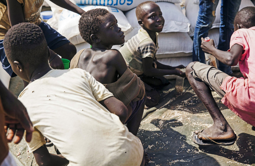 Young boys gather leftover grain at a food distribution site at the Imvepi refugee camp in Northern Uganda as refugees lineup to claim their monthly rations on Saturday, 24 June, 2017.