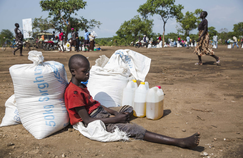 A young man waits with his families monthly rations at a food distribution site at the Imvepi refugee camp in Northern Uganda as on Saturday, 24 June, 2017.